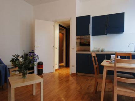 The apartment, featuring parquet flooring, opens up onto a small hallway leading to a bathroom with shower and to the living area, furnished with a fully equipped kitchen, a dining area with a table f